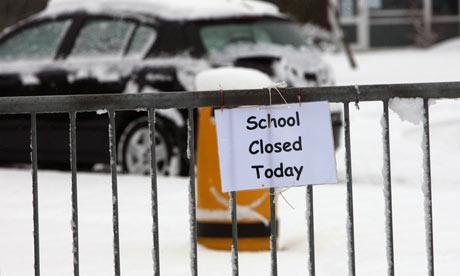 snowy day with school closed today sign on fence